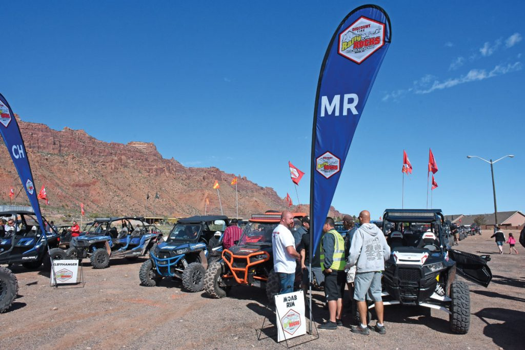 New for 2016, flags marked the line-up points for each police-escorted ride, and each ride was limited by the BLM to 25 rally-goers and 10 guides/vendors. These are the Moab Rim and Cliffhanger lines, which made a long parade through town to the trailheads.