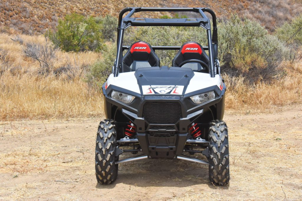 Up front the RZR 900 has 10 inches of travel, LED headlights, a front torsion bar, dual-bore front brake calipers squeezing perforated rotors, and CV boot guards on the tubular front A-arms. The 26x8-12 PXT tires ride on cast-aluminum rims.