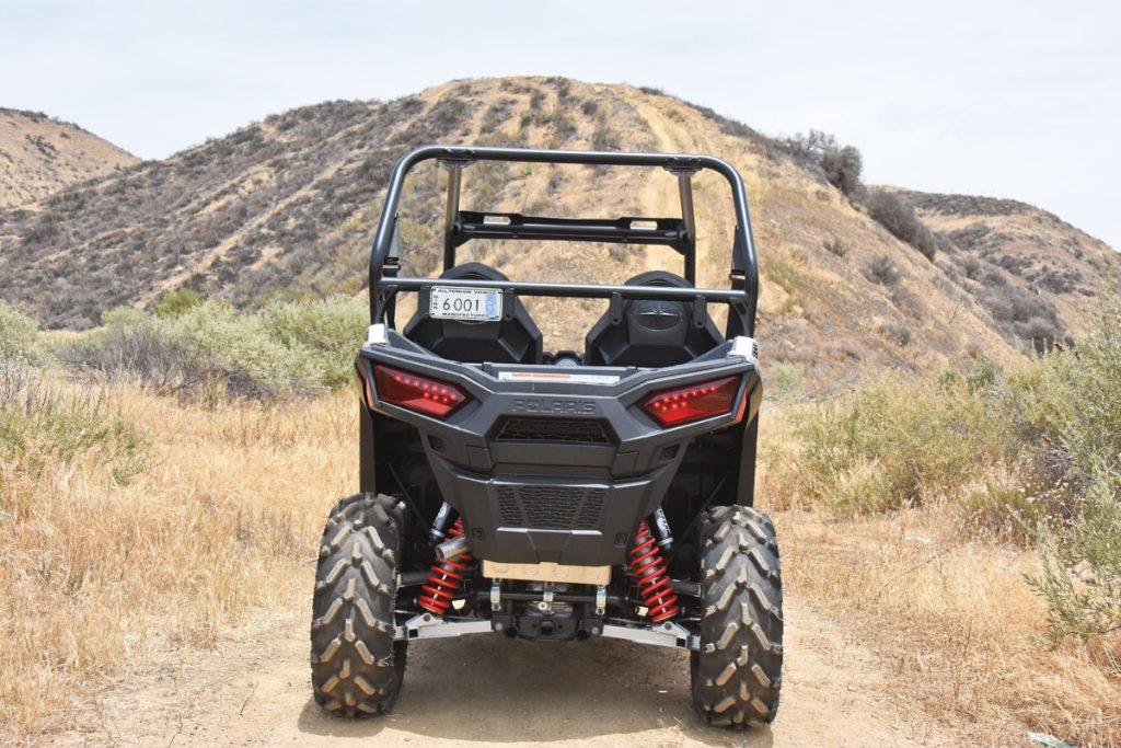 Rear 26x9-12 PXT tires ride on wider rims, and dual-A-arm IRS delivers 10 inches of travel with a 43-inch rear track width. Unlike the cab-sharing RZR XPs, the RZR 900 has a 1.25-inch receiver and a 1500-pound tow rating. Check out the massive rear torsion bar.