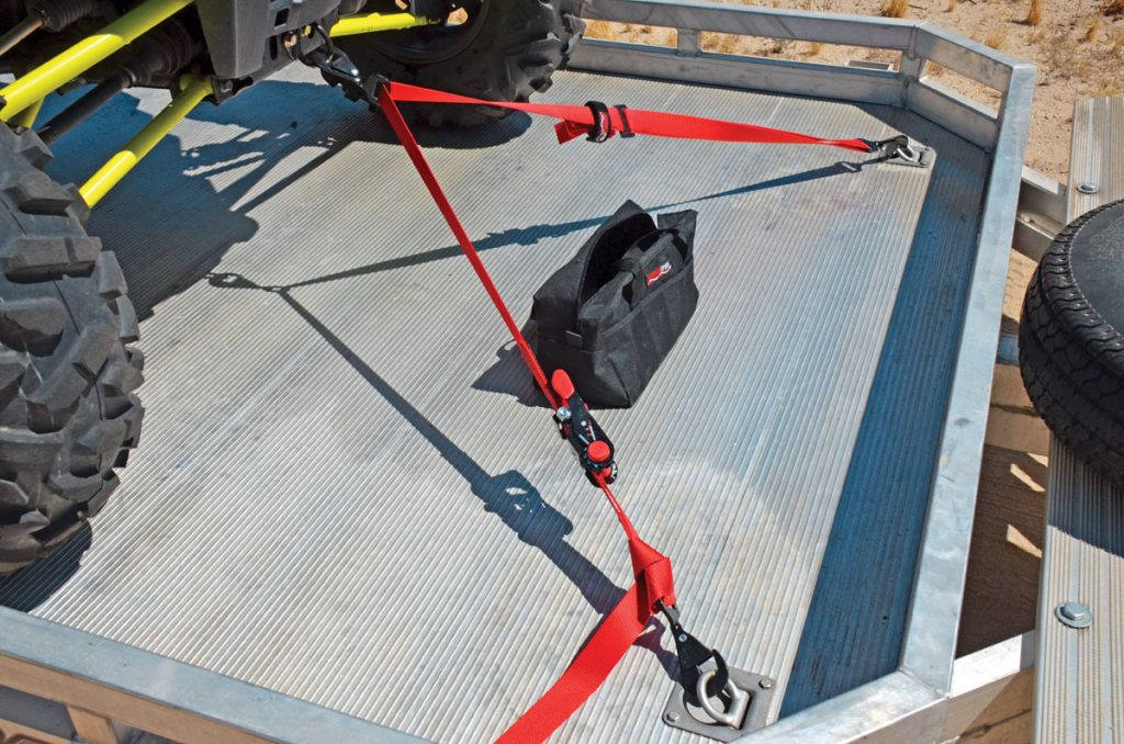 The SpeedStrap UTV 1.5-inch, three-point ratchet tie-down has a floating, twisted snap hook with springloaded safety lock like the two end hooks. The 12-foot SpeedStrap is available in red or black. The RZR XP 1000 tie-down kit's front D-ring attaches to the mount for RZR accessory bumpers, so it's not compatible with low-profile Bull or Extreme bumpers.