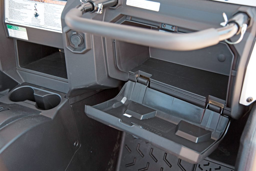 A large, latched glove box rides under the cushioned grab bar with three-position adjustment, and the cup holders and center cubby hole are handy. Cabin comfort is very high, and noise and vibration are low.