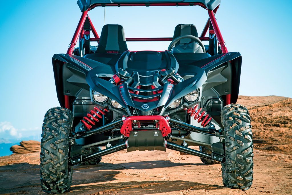 Maxxis 27x9R14 Bighorn 2.0 front tires ride on aluminum beadlock wheels, and the sloped hood gives it a better sight line in dunes, hills and rocks than a RZR XP, despite a lower seating position in the YXZ1000R. CVs are 9mm smaller yet have a stronger CV boot. Rear arms got CV guards like the front for 2017.