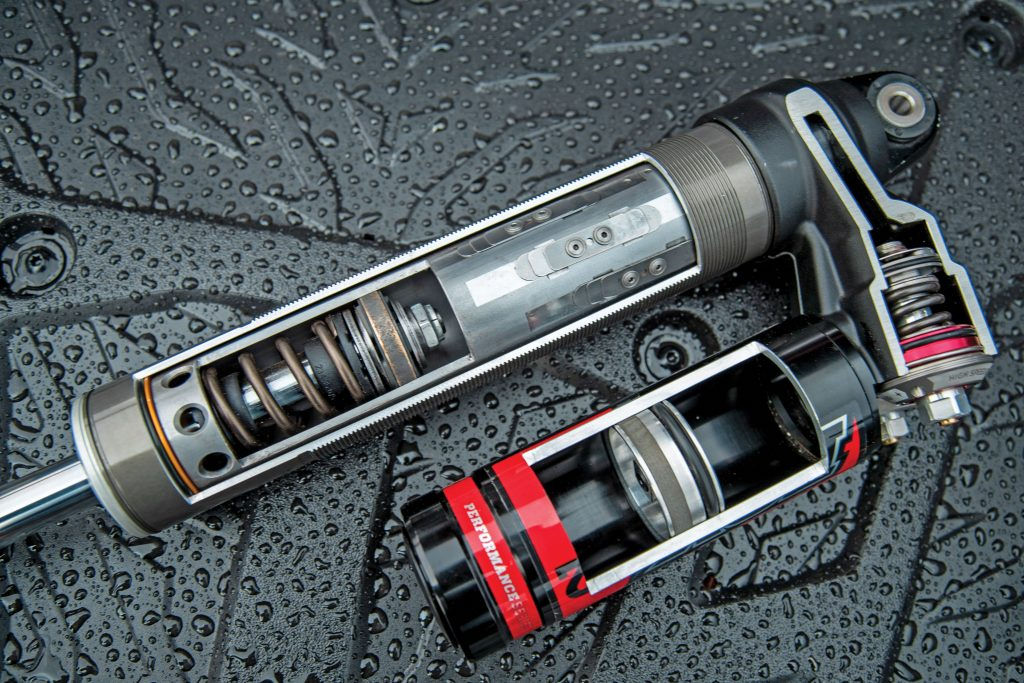 Here's the magic: Fox 2.5 Podium X2 shocks have Internal ByPass and Bottom-Out Control technology, and the main piston valves only open at bottoming. Dual-speed compression and rebound adjusters on the piggybacks do most of the fluid damping, along with the IBP reeds/ports, during travel.
